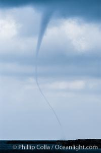 The early stage of a waterspout, in which a funnel descends from clouds down toward the ocean surface.  Note the thin curved vortex of the waterspout, it is not yet mature.  Waterspouts are tornados that form over water