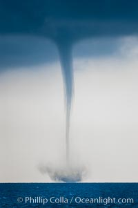 A mature waterspout, seen extending from clouds above to the ocean surface.  A significant disturbance on the ocean is clearly visible, the waterspout has reached is maximum intensity.   Waterspouts are tornadoes that form over water, Great Isaac Island
