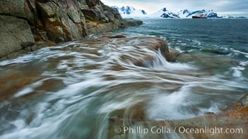 Waves rush in, sunset, Antarctica.  Ocean water rushes ashore over the rocky edge of Peterman Island, Antarctica. Peterman Island, Antarctic Peninsula, Antarctica, natural history stock photograph, photo id 25610
