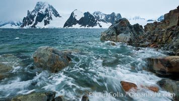 Waves rush in, sunset, Antarctica.  Ocean water rushes ashore over the rocky edge of Peterman Island, Antarctica. Peterman Island, Antarctic Peninsula, Antarctica, natural history stock photograph, photo id 25629