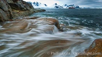 Image 25636, Waves rush in, sunset, Antarctica.  Ocean water rushes ashore over the rocky edge of Peterman Island, Antarctica. Peterman Island, Antarctic Peninsula, Antarctica, Phillip Colla, all rights reserved worldwide. Keywords: antarctic peninsula, antarctica, oceans, peterman island, petermann island, southern ocean.