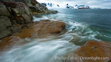 Waves rush in, sunset, Antarctica.  Ocean water rushes ashore over the rocky edge of Peterman Island, Antarctica