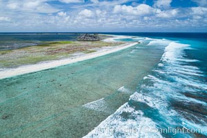 Waves break on the coral reef and wash ashore at Clipperton Island, aerial photo. Clipperton Island, a minor territory of France also known as Ile de la Passion, is a spectacular coral atoll in the eastern Pacific. By permit HC / 1485 / CAB (France)