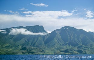 West Maui mountains rise above the coast of Maui, with clouds flanking the ancient eroded remnants of a volcano