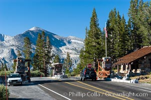 A car enters the stunning High Sierra entrance to Yosemite National Park at the summit of Tioga Pass. Mammoth Peak is seen in the background. A lucky park ranger, whose office is perhaps more beautiful than any other in the world, greets each car as it passes through. Tuolumne Meadows area of Yosemite National Park