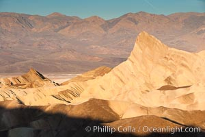 Image 15602, Zabriskie Point, sunrise.  Manly Beacon rises in the center of an eroded, curiously banded area of sedimentary rock, with the Panamint Mountains visible in the distance. Death Valley National Park, California, USA, Phillip Colla, all rights reserved worldwide.   Keywords: california:death valley:death valley national park:desert:environment:landscape:manly beacon:national park:national parks:nature:outdoors:outside:scene:scenery:scenic:usa:zabriskie point.