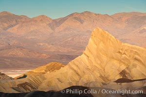 Zabriskie Point, sunrise.  Manly Beacon rises in the center of an eroded, curiously banded area of sedimentary rock, with the Panamint Mountains visible in the distance. Death Valley National Park, California, USA, natural history stock photograph, photo id 15618
