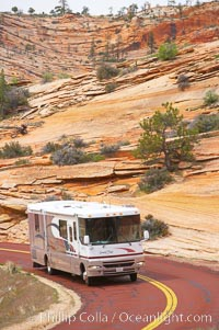 A motorhome recreational vehicle RV travels through the red rocks of Zion National Park