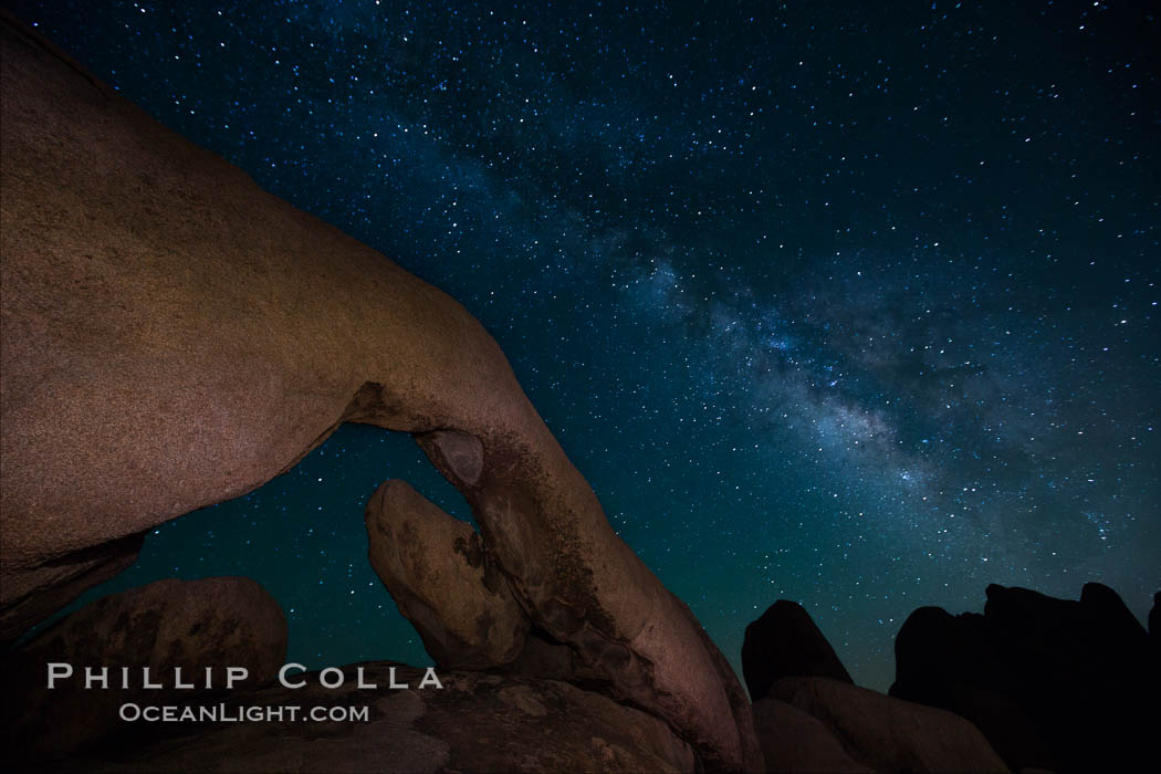 The Milky Way galaxy arcs over Arch Rock on a clear evening in Joshua Tree National Park. Joshua Tree National Park, California, USA, natural history stock photograph, photo id 27800