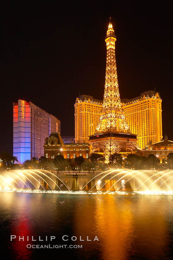 Image 20579, The Bellagio Hotel fountains light up the reflection pool as the half-scale replica of the Eiffel Tower at the Paris Hotel in Las Vegas rises above them, at night. Las Vegas, Nevada, USA