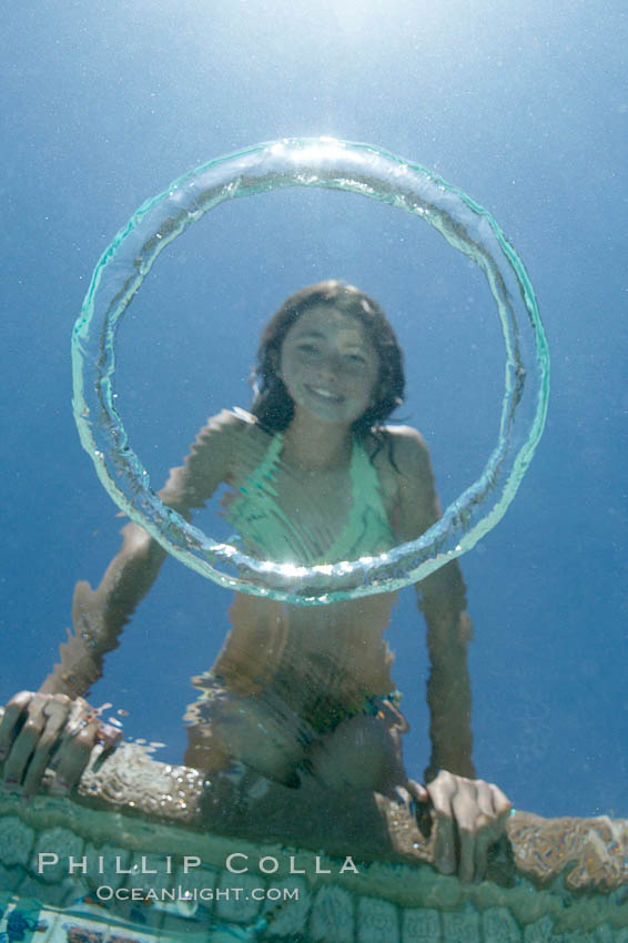 A bubble ring. A young girl watches as a bubble ring ascends through the water toward her., natural history stock photograph, photo id 20776