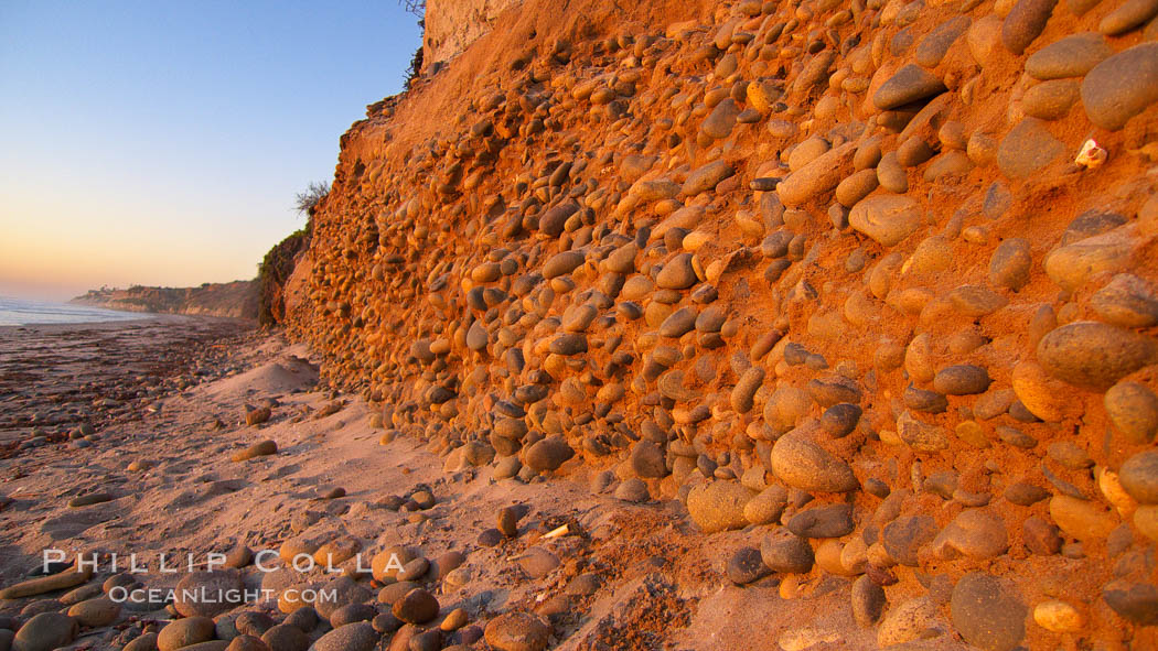 Cobblestones fall to the sand beach from the sandstone cliffs in which they are embedded. Carlsbad, California, USA, natural history stock photograph, photo id 21774