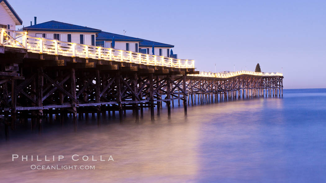 The Crystal Pier and Pacific Ocean at sunrise, dawn, waves blur as they crash upon the sand.  Crystal Pier, 872 feet long and built in 1925, extends out into the Pacific Ocean from the town of Pacific Beach. Pacific Beach, California, USA, natural history stock photograph, photo id 27240