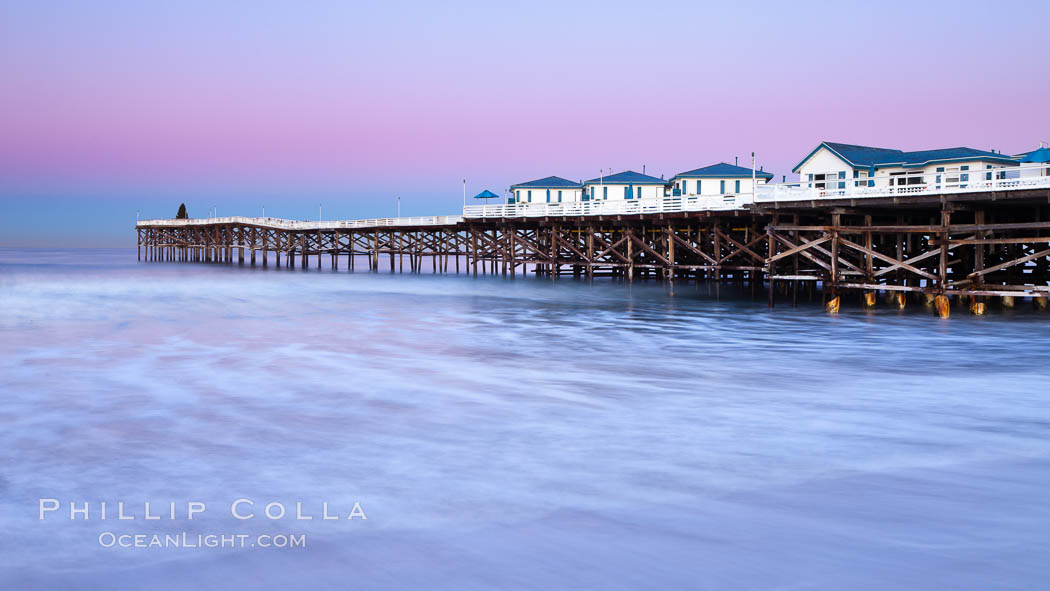 The Crystal Pier and Pacific Ocean at sunrise, dawn, waves blur as they crash upon the sand.  Crystal Pier, 872 feet long and built in 1925, extends out into the Pacific Ocean from the town of Pacific Beach. Pacific Beach, California, USA, natural history stock photograph, photo id 27243