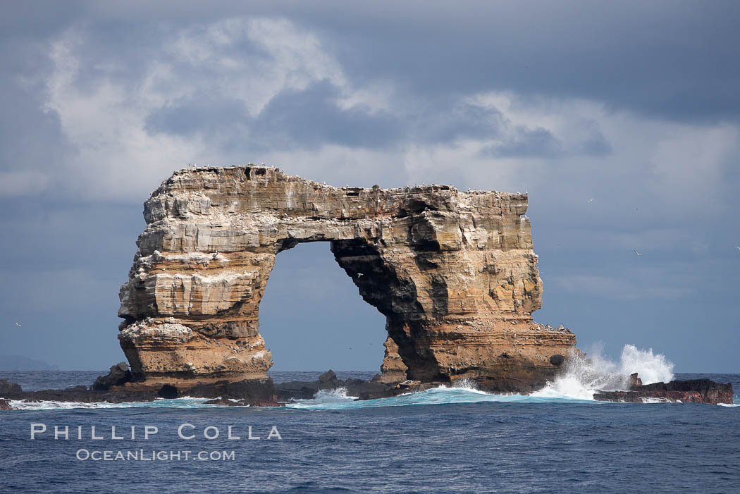 Darwins Arch, a dramatic 50-foot tall natural lava arch, rises above the ocean a short distance offshore of Darwin Island. Galapagos Islands, Ecuador, natural history stock photograph, photo id 16652