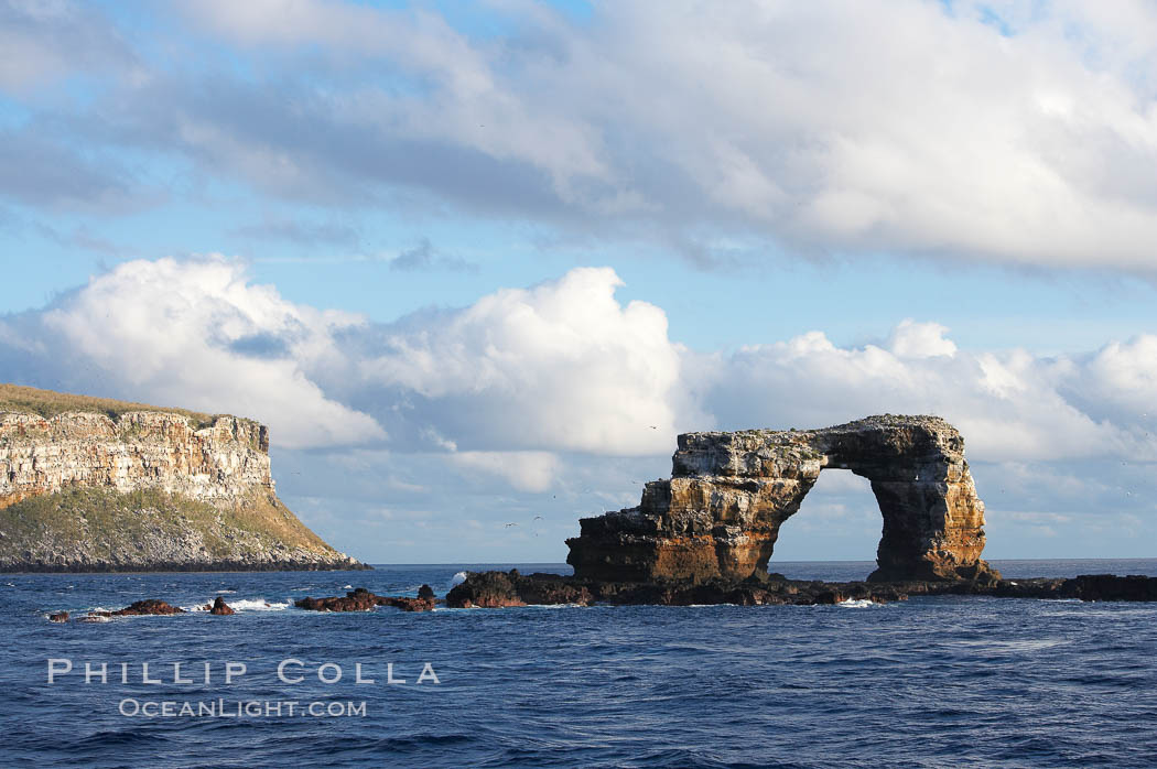 Darwins Arch, a dramatic 50-foot tall natural lava arch, rises above the ocean a short distance offshore of Darwin Island. Galapagos Islands, Ecuador, natural history stock photograph, photo id 16653