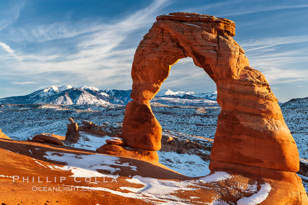 Delicate Arch, dusted with snow, at sunset, with the snow-covered La Sal mountains in the distance.  Delicate Arch stands 45 feet high, with a span of 33 feet, atop of bowl of slickrock sandstone. Delicate Arch, Arches National Park, Utah, USA, natural history stock photograph, photo id 18104