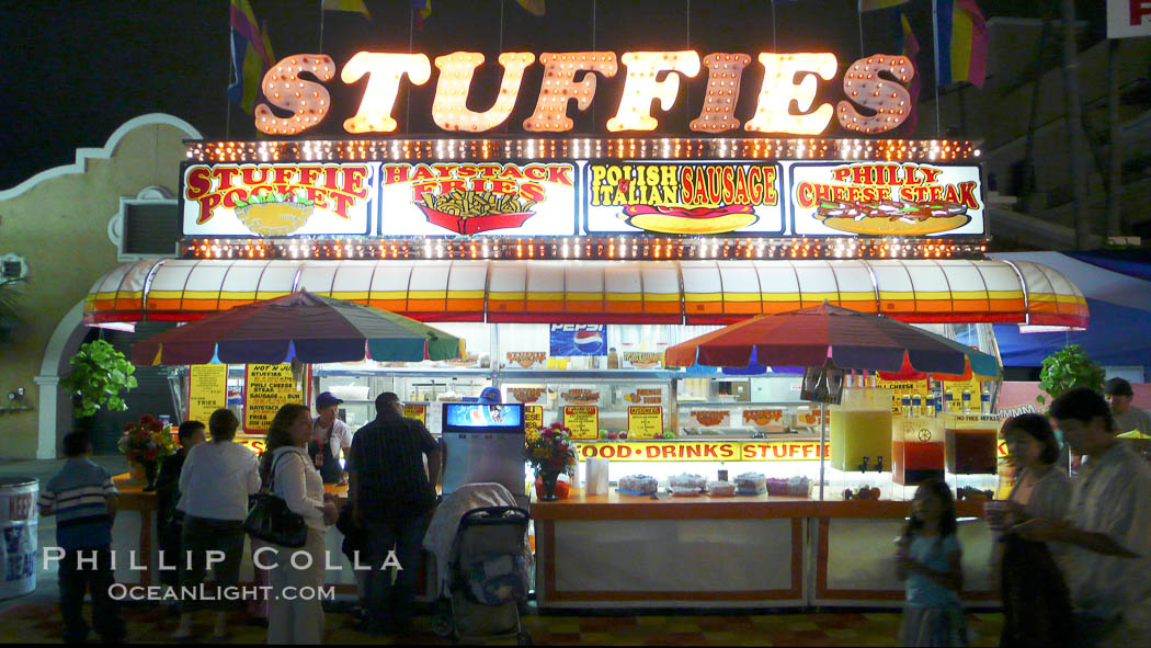 Food vendors at the Del Mar Fair, famous for their tasty, greasy, salty, fattening and generally unwholesome food, which visitors eat by the ton.  Bright lights at night. Del Mar Fair, Del Mar, California, USA, natural history stock photograph, photo id 20880