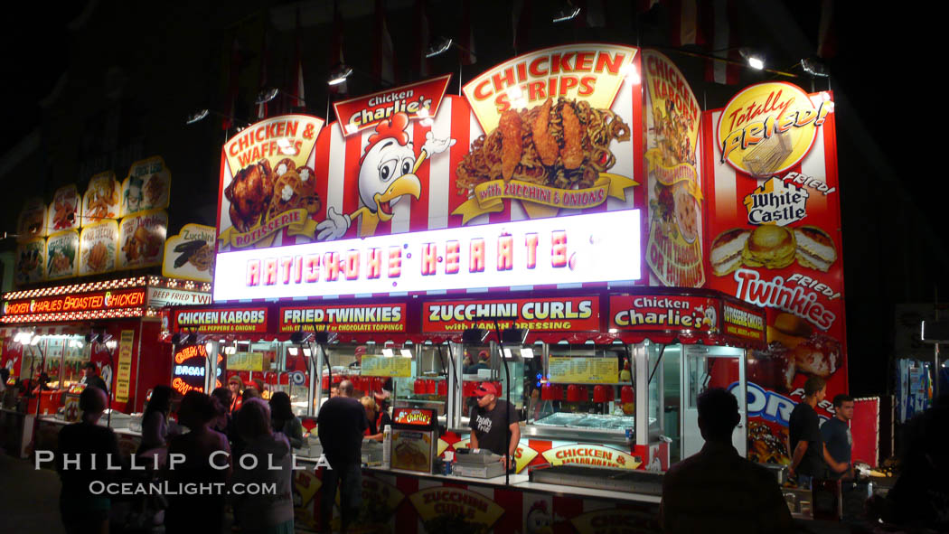 Food vendors at the Del Mar Fair, famous for their tasty, greasy, salty, fattening and generally unwholesome food, which visitors eat by the ton.  Bright lights at night. Del Mar Fair, Del Mar, California, USA, natural history stock photograph, photo id 20881