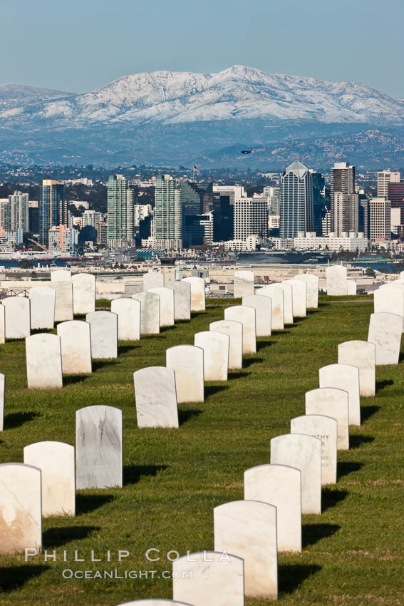 Tombstones at Fort Rosecrans National Cemetery, with downtown San Diego with snow-covered Mt. Laguna in the distance. California, USA, natural history stock photograph, photo id 26574