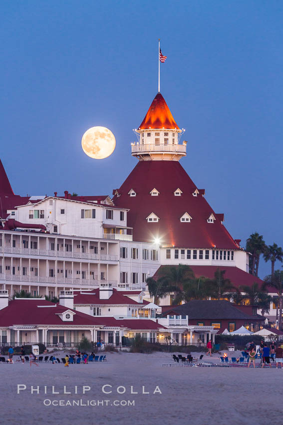 Full Moon Rising over Hotel del Coronado, known affectionately as the Hotel Del. It was once the largest hotel in the world, and is one of the few remaining wooden Victorian beach resorts. It sits on the beach on Coronado Island, seen here with downtown San Diego in the distance. It is widely considered to be one of Americas most beautiful and classic hotels. Built in 1888, it was designated a National Historic Landmark in 1977. San Diego, California, USA, natural history stock photograph, photo id 29420