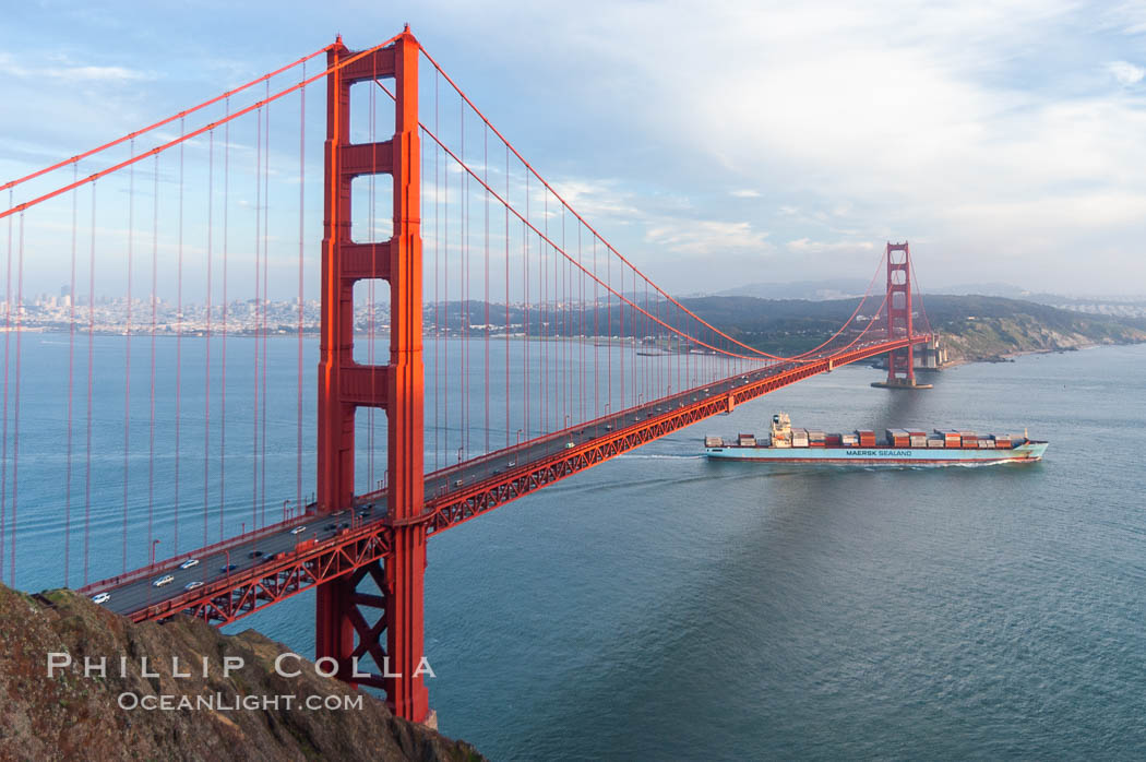 A container ship leaves San Francisco Bay, passing under the Golden Gate Bridge, viewed from the Marin Headlands with the city of San Francisco in the distance.  Late afternoon. California, USA, natural history stock photograph, photo id 09050