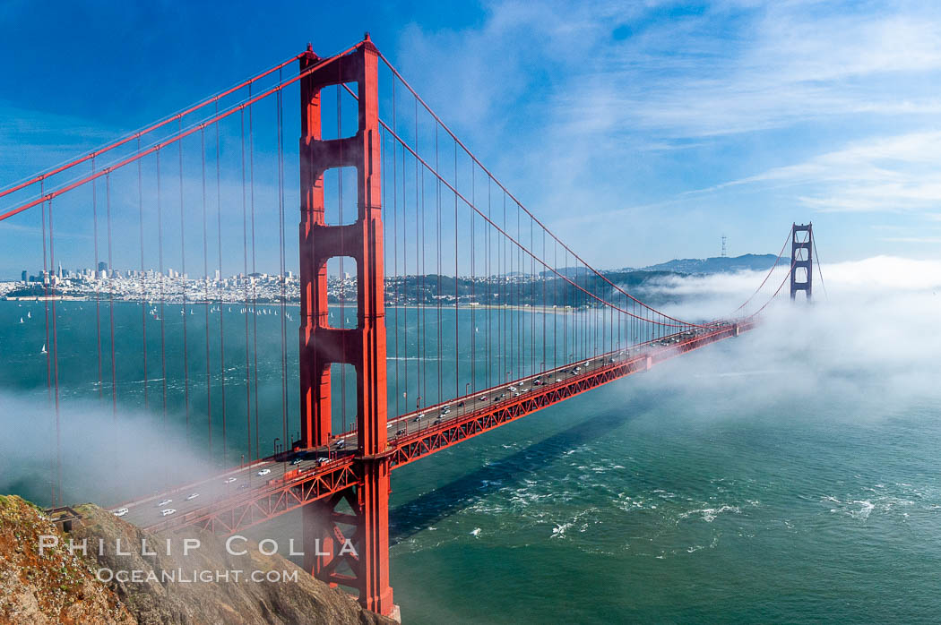 San Franciscos infamous summer fog overtakes the Golden Gate Bridge, viewed from the Marin Headlands with the city of San Francisco visible in the distance. California, USA, natural history stock photograph, photo id 09066