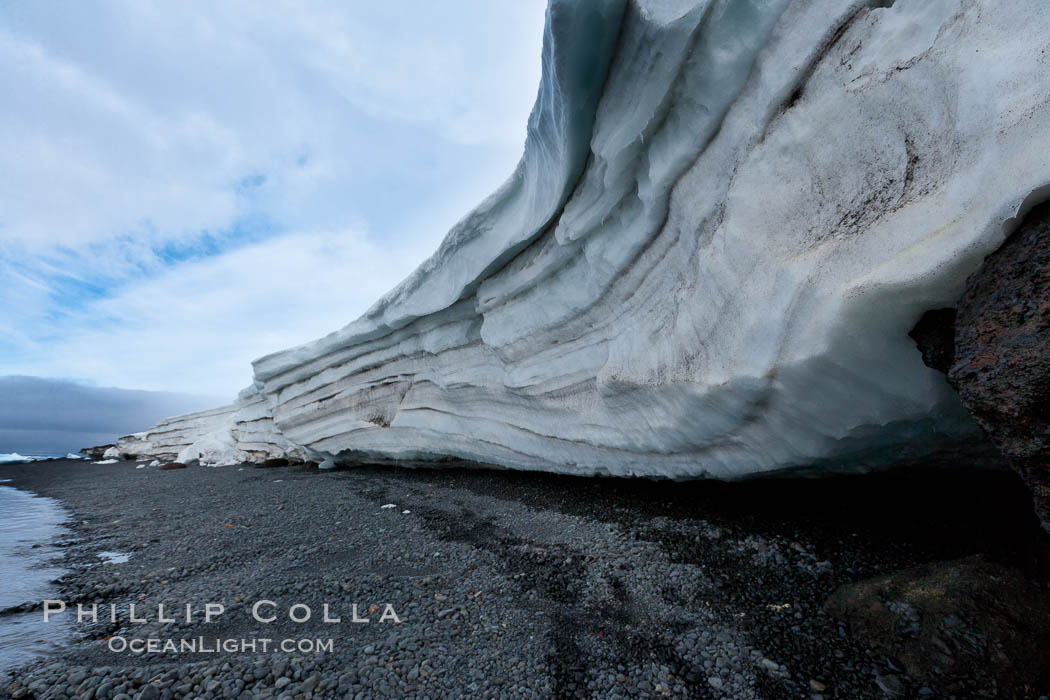 Horizontal striations and layers in packed snow, melting and overhanging, seen from the edge of the snowpack, along a rocky beach. Brown Bluff, Antarctic Peninsula, Antarctica, natural history stock photograph, photo id 24782