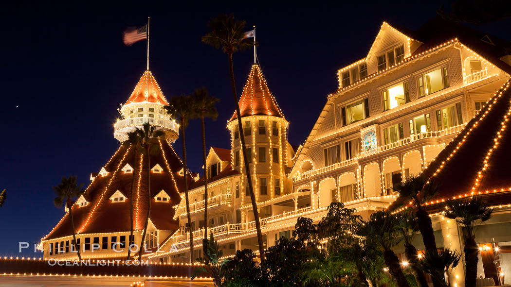 Hotel del Coronado with holiday Christmas night lights, known affectionately as the Hotel Del. It was once the largest hotel in the world, and is one of the few remaining wooden Victorian beach resorts. It sits on the beach on Coronado Island, seen here with downtown San Diego in the distance. It is widely considered to be one of Americas most beautiful and classic hotels. Built in 1888, it was designated a National Historic Landmark in 1977. San Diego, California, USA, natural history stock photograph, photo id 27404