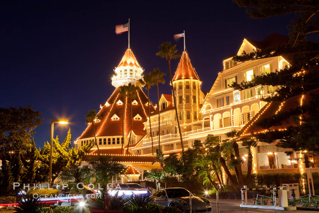 Hotel del Coronado with holiday Christmas night lights, known affectionately as the Hotel Del. It was once the largest hotel in the world, and is one of the few remaining wooden Victorian beach resorts. It sits on the beach on Coronado Island, seen here with downtown San Diego in the distance. It is widely considered to be one of Americas most beautiful and classic hotels. Built in 1888, it was designated a National Historic Landmark in 1977. California, USA, natural history stock photograph, photo id 27405