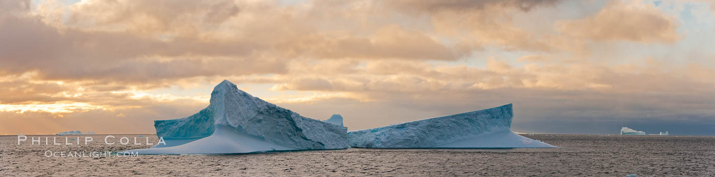 Iceberg panoramic photo.  Iceberg, ocean, light and clouds. Light plays over icebergs and the ocean near Coronation Island. South Orkney Islands, Southern Ocean, natural history stock photograph, photo id 26308