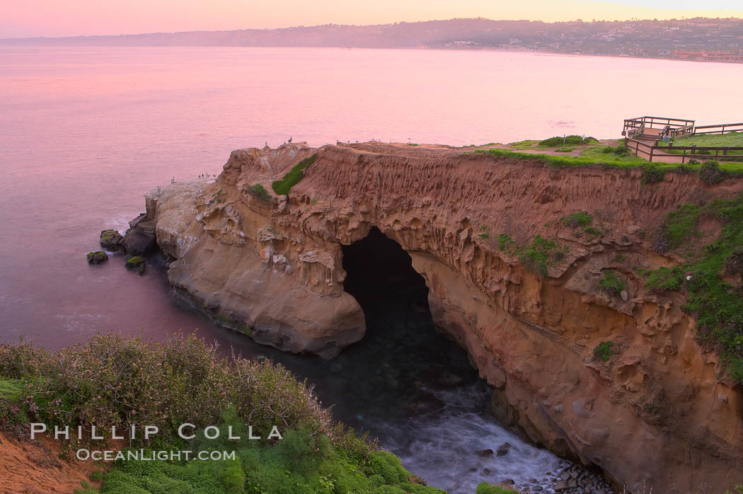 A large natural sea cave lies below a sandstone bluff in La Jolla at sunrise with a pink sky, Black's Beach in the distant. California, USA, natural history stock photograph, photo id 20250