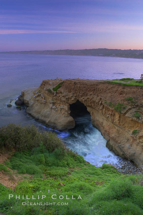 A large natural sea cave lies below a sandstone bluff in La Jolla at sunrise with a pink sky, Black's Beach in the distant. La Jolla, California, USA, natural history stock photograph, photo id 20252