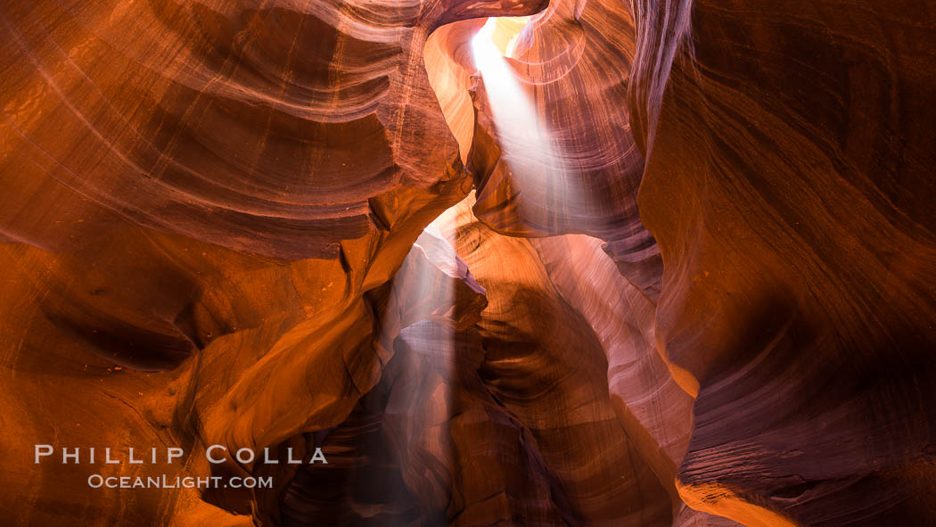Light Beam in Upper Antelope Slot Canyon.  Thin shafts of light briefly penetrate the convoluted narrows of Upper Antelope Slot Canyon, sending piercing beams through the sandstone maze to the sand floor below. Navajo Tribal Lands, Page, Arizona, USA, natural history stock photograph, photo id 28564