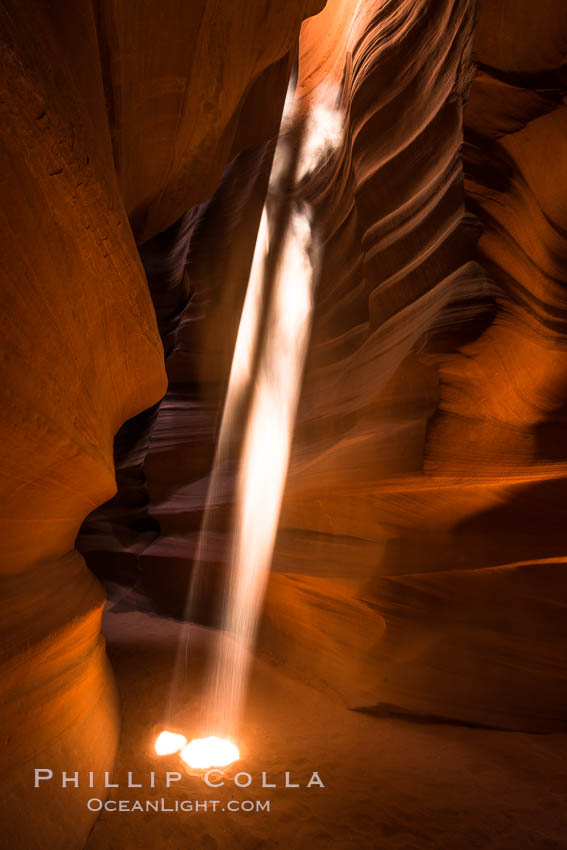 Light Beam in Upper Antelope Slot Canyon.  Thin shafts of light briefly penetrate the convoluted narrows of Upper Antelope Slot Canyon, sending piercing beams through the sandstone maze to the sand floor below. Navajo Tribal Lands, Page, Arizona, USA, natural history stock photograph, photo id 28573