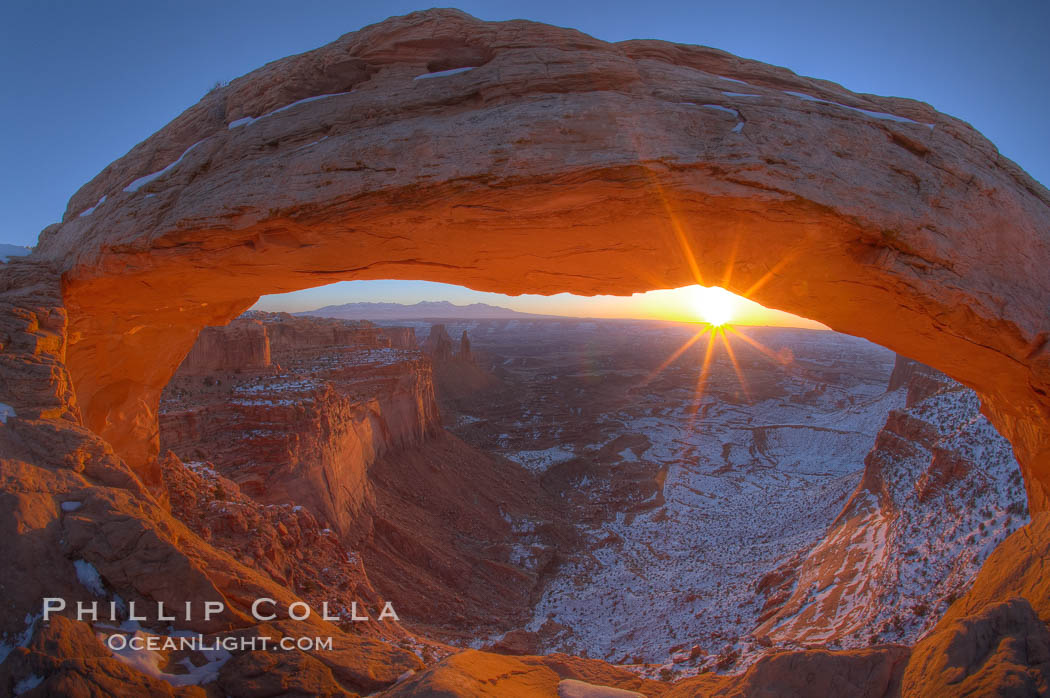 Mesa Arch spans 90 feet and stands at the edge of a mesa precipice thousands of feet above the Colorado River gorge. For a few moments at sunrise the underside of the arch glows dramatically red and orange. Island in the Sky, Canyonlands National Park, Utah, USA, natural history stock photograph, photo id 18041