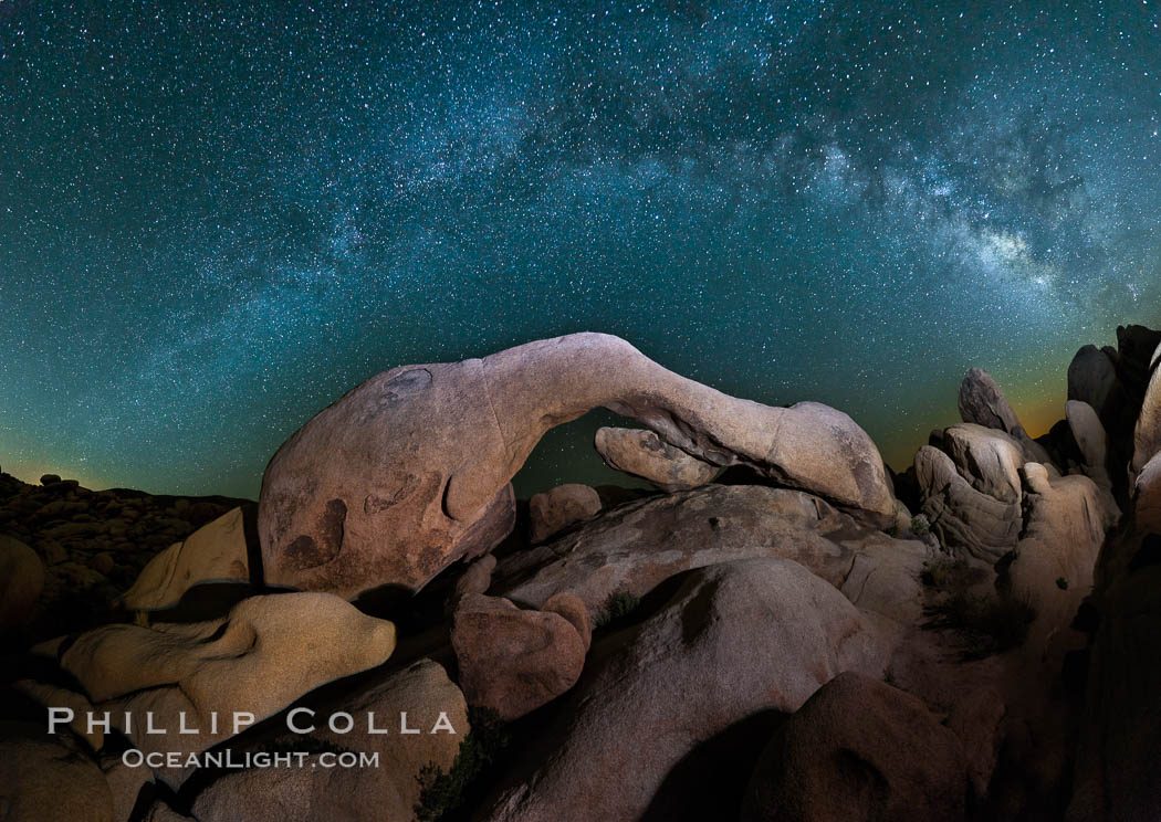 The Milky Way galaxy arches over Arch Rock on a clear evening in Joshua Tree National Park. Joshua Tree National Park, California, USA, natural history stock photograph, photo id 26796