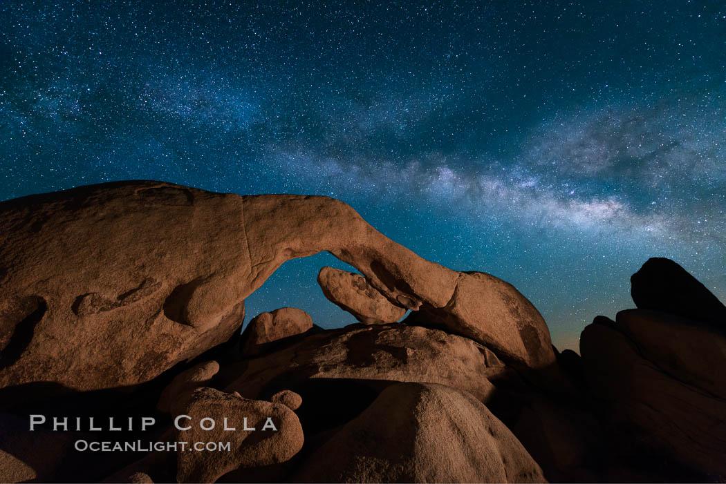The Milky Way stretches across the sky above Arch Rock in Joshua Tree National Park. Joshua Tree National Park, California, USA, natural history stock photograph, photo id 28407