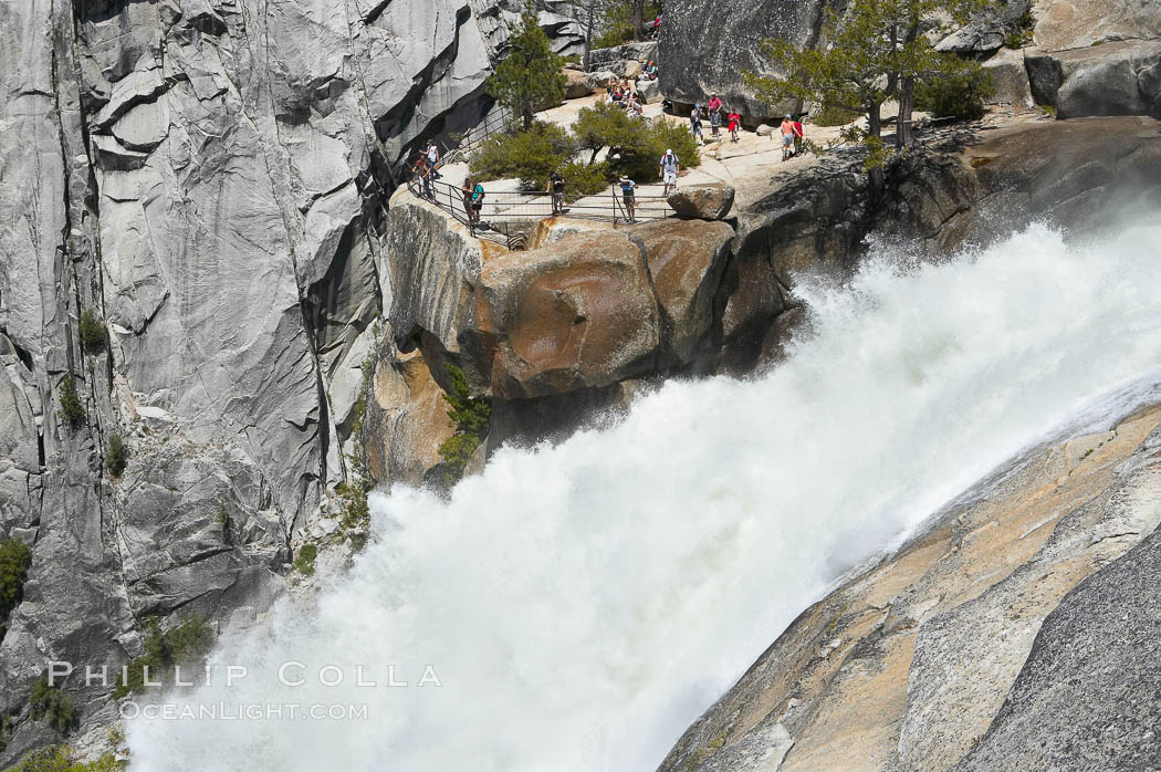 The brink of Nevada Falls, with hikers visible at the precipice. Nevada Falls marks where the Merced River plummets almost 600 through a joint in the Little Yosemite Valley, shooting out from a sheer granite cliff and then down to a boulder pile far below. Nevada Falls, Yosemite National Park, California, USA, natural history stock photograph, photo id 16121