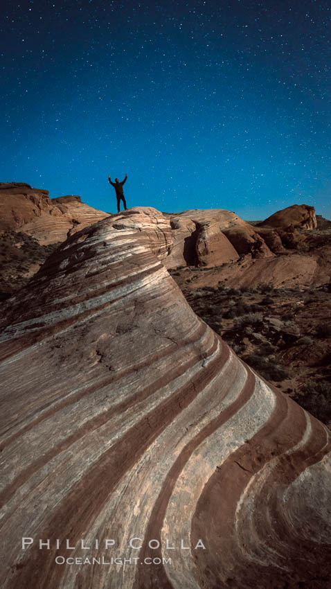 Exuberant hiker atop the Fire Wave, at night, stars and the evening sky. Valley of Fire State Park, Nevada, USA, natural history stock photograph, photo id 28450