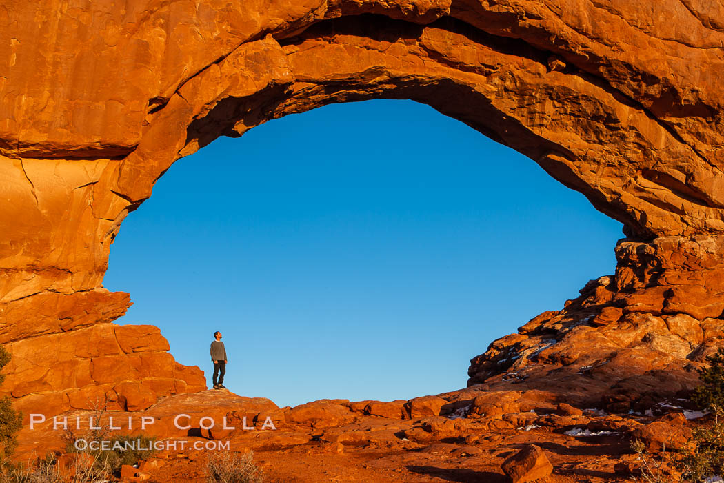 Hiker in North Window, sunset, western face.  North Window is a natural sandstone arch 90 feet wide and 48 feet high. Arches National Park, Utah, USA, natural history stock photograph, photo id 18160