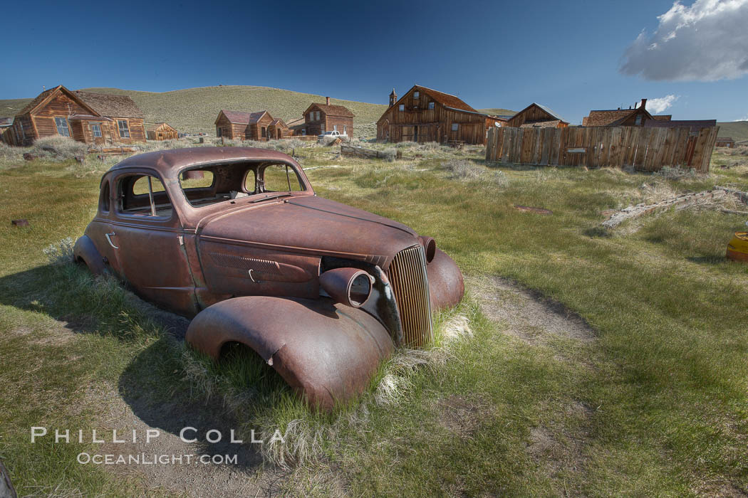 Image 23134, Old car lying in dirt field, Fuller Street and Green Street buildings in background. Bodie State Historical Park, California, USA, Phillip Colla, all rights reserved worldwide. Keywords: arrested decay, bodie, bodie ghost town, bodie state historic park, bodie state historical park, bridgeport, california, eastern sierra, ghost town, gold mine, gold mining, gold rush, historic state park, mining camp, mining town, old west, outdoors, outside, sierra, state park, state parks, town, usa, village, west.