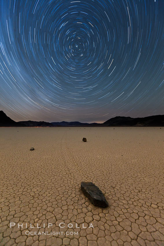 Racetrack sailing stone and star trails.  A sliding rock of the Racetrack Playa. The sliding rocks, or sailing stones, move across the mud flats of the Racetrack Playa, leaving trails behind in the mud. The explanation for their movement is not known with certainty, but many believe wind pushes the rocks over wet and perhaps icy mud in winter. Racetrack Playa, Death Valley National Park, California, USA, natural history stock photograph, photo id 27668