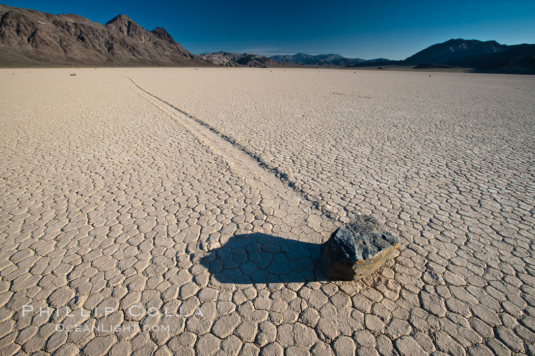 Sailing stone on the Death Valley Racetrack playa.  The sliding rocks, or sailing stones, move across the mud flats of the Racetrack Playa, leaving trails behind in the mud.  The explanation for their movement is not known with certainty, but many believe wind pushes the rocks over wet and perhaps icy mud in winter. Death Valley National Park, California, USA, natural history stock photograph, photo id 25321