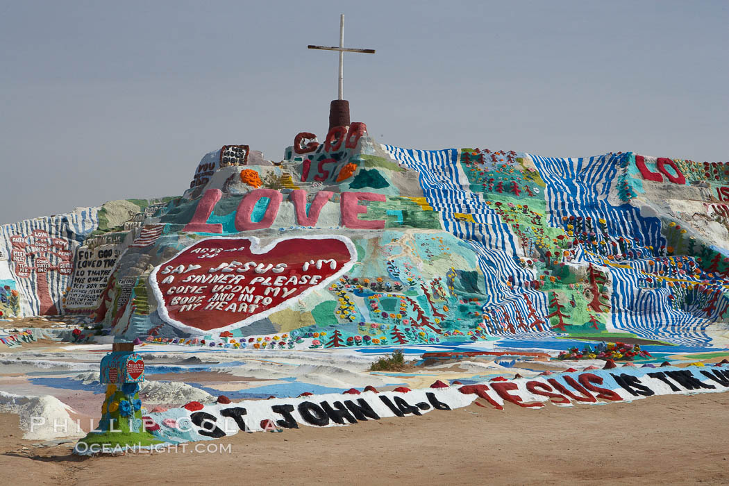"Salvation Mountain, near the desert community of Slab City and the small town of Niland on the east side of the Salton Sea.  Built over several decades by full-time resident Leonard Knight, who lives at the site, Salvation Mountain was built from over 100,000 gallons of paint, haybales, wood and metal and was created by Mr. Knight to convey the message that ""God Loves Everyone"". California, USA, natural history stock photograph, photo id 22504"