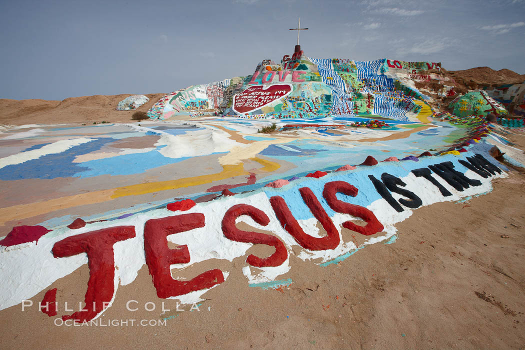 "Salvation Mountain, near the desert community of Slab City and the small town of Niland on the east side of the Salton Sea.  Built over several decades by full-time resident Leonard Knight, who lives at the site, Salvation Mountain was built from over 100,000 gallons of paint, haybales, wood and metal and was created by Mr. Knight to convey the message that ""God Loves Everyone"". California, USA, natural history stock photograph, photo id 22513"