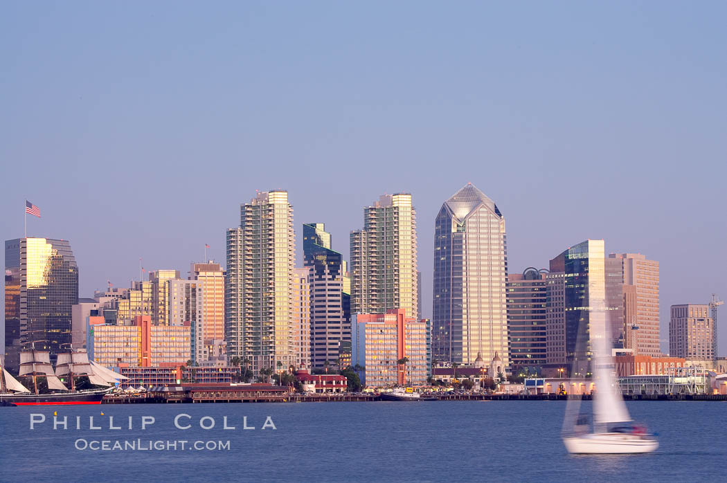 San Diego city skyline at dusk, viewed from Harbor Island, a sailboat cruises by in the foreground, the Star of India at left. California, USA, natural history stock photograph, photo id 14535