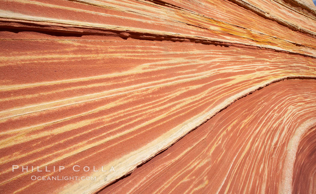 Image 20631, The Wave, an area of fantastic eroded sandstone featuring beautiful swirls, wild colors, countless striations, and bizarre shapes set amidst the dramatic surrounding North Coyote Buttes of Arizona and Utah.  The sandstone formations of the North Coyote Buttes, including the Wave, date from the Jurassic period. Managed by the Bureau of Land Management, the Wave is located in the Paria Canyon-Vermilion Cliffs Wilderness and is accessible on foot by permit only. North Coyote Buttes, Paria Canyon-Vermilion Cliffs Wilderness, Arizona, USA, Phillip Colla, all rights reserved worldwide. Keywords: arizona, barren, butte, cliffs, desert, diagenic coloration, environment, erosion, geology, landmark, landscape, layers, national parks, nature, north coyote buttes, outdoors, outside, paria, paria canyon vermilion cliffs wilderness, paria canyon-vermilion cliffs wilderness, rock, sandstone, scene, scenic, sedimentary, sedimentary rock, stratigraphic relationship, the wave, usa, vermilion, vermilion cliffs national monument, vermillion, wave coyote buttes, wilderness.