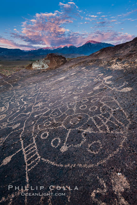 Sky Rock petroglyphs near Bishop, California, sunrise light just touching clouds and the Sierra Nevada. Hidden atop an enormous boulder in the Volcanic Tablelands lies Sky Rock, a set of petroglyphs that face the sky.  These superb examples of native American petroglyph artwork are thought to be Paiute in origin, but little is known about them. Bishop, California, USA, natural history stock photograph, photo id 26979