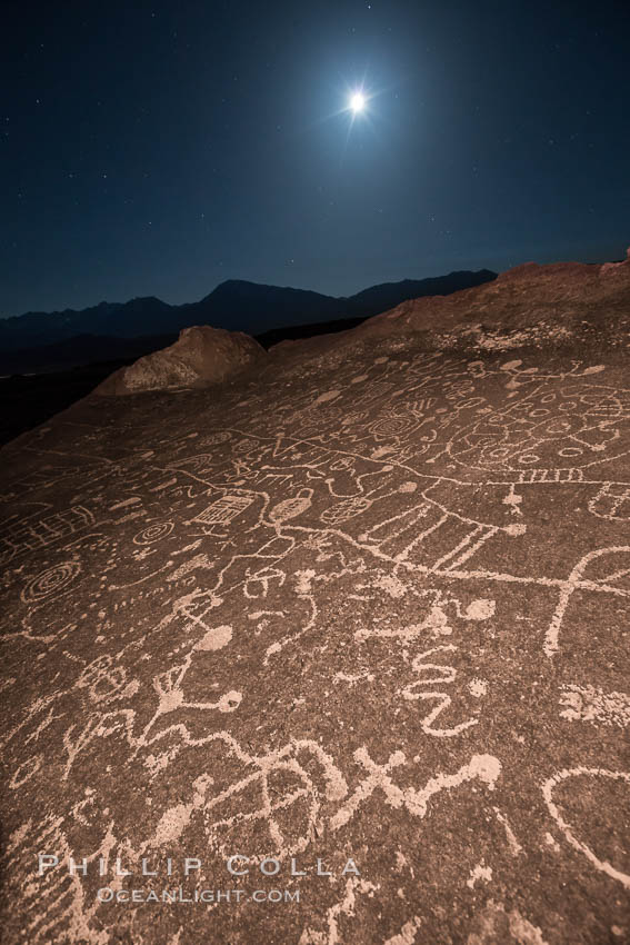 Sky Rock at night, light by moonlight with stars in the clear night sky above.  Sky Rock petroglyphs near Bishop, California. Hidden atop an enormous boulder in the Volcanic Tablelands lies Sky Rock, a set of petroglyphs that face the sky. These superb examples of native American petroglyph artwork are thought to be Paiute in origin, but little is known about them., natural history stock photograph, photo id 28504